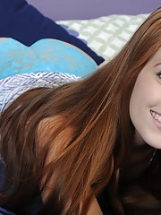 Innocent-looking redhead with blue panties masturbating on a bed