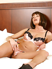 Bobcut brunette MILF teasing her pussy with a golden toy on a bed